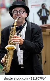 AURILLAC, FRANCE - AUGUST 23: saxophonist playing in the street as part of the Aurillac International Street Theater Festival, Company Histoire de famille ,on august 23, 2012, in Aurillac,France.