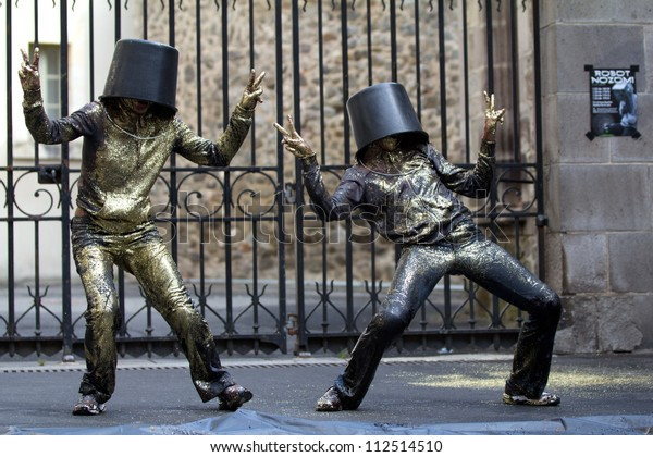 AURILLAC, FRANCE - AUGUST 23: Two dancers with a bucket on the head as part of the Aurillac International Street Theater Festival, show named Vachement, on august 23, 2012, in Aurillac,France.