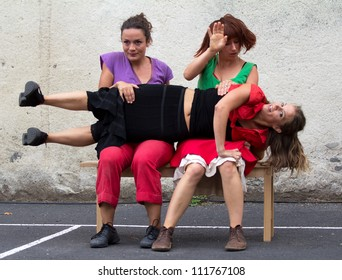 AURILLAC, FRANCE - AUGUST 24 : a dancer is lying on the knees of two women, Aurillac International Street Theater Festival, Company D'Akipaya Danza , on august 24, 2012, in Aurillac,France.