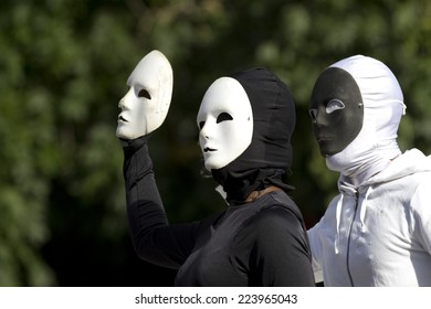 AURILLAC, FRANCE-AUGUST 25: two masked people play with their black and white masks as part of the Aurillac International Street Theater Festival, cie Bakhus 24,on august 25,2014, in Aurillac,France.