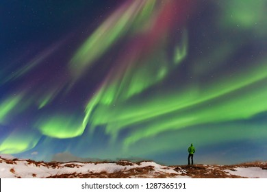 Aurora borealis above the silhouette man. Jokulsarlon glacier lagoon, Iceland. Green northern lights. Starry sky with polar lights. Night winter landscape with aurora