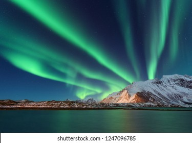 Aurora borealis above the snow covered mountain in Lofoten islands, Norway. Northern lights in winter. Night landscape with polar lights, snowy rocks, reflection in the sea. Starry sky with aurora