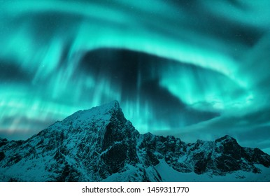 Aurora borealis above the snow covered mountain peak in Lofoten islands, Norway. Northern lights in winter. Night landscape with polar lights, snowy rocks. Starry sky with aurora. Beautiful nature