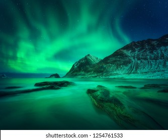 Aurora borealis above snowy mountain and sandy beach with stones. Northern lights in Lofoten islands, Norway. Starry sky with polar lights. Night winter landscape with aurora, sea with blurred water