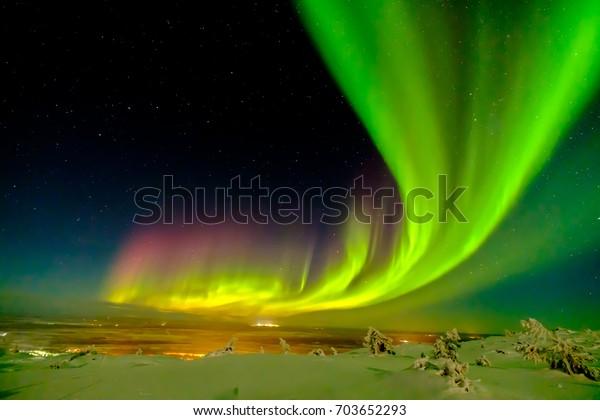 Aurora borealis (также известный как северное или полярное сияние) за полярным кругом в зимней Лапландии.