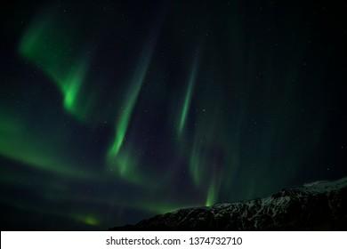 Aurora Borealis behind a snowy mountain