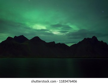 Aurora borealis in cloudy sky over the dark mountains