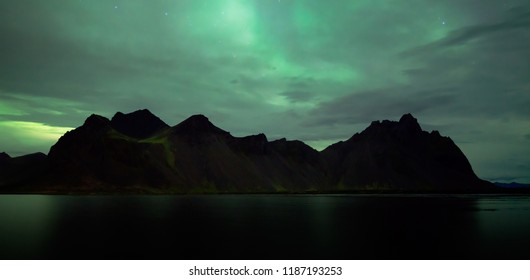 Aurora borealis in cloudy sky over the Vestrahorn, Iceland