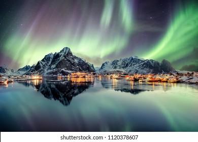 Aurora borealis dancing on mountain in fishing village at Reine, Lofoten, Norway