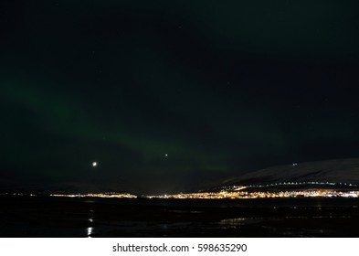 aurora borealis dancing over snowy mountain and fjord landscape with full moon light