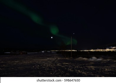 aurora borealis dancing over snowy field near sea shore with full moon