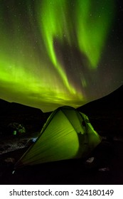 Aurora Borealis green spiral splash above a small and lightweight expedition tent in Malaya Belaya river valley of Hibiny mountains