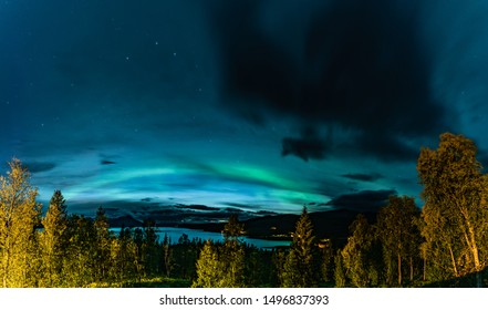 Aurora Borealis and heavy clouds over Norwegian mountains around Rossvatnet Lake, Northern Norway. Late summer night.