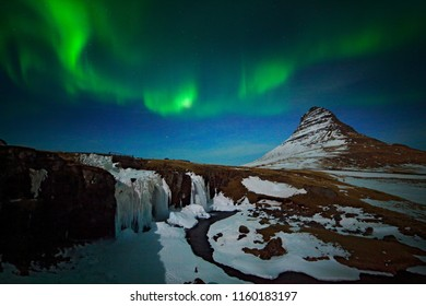 Aurora Borealis from Iceland. Beautiful green Northern Lights on the dark blue night sky with peak with snow, Kirkjufell, Iceland. Winter landscape during the night. Ice waterfall with hill.