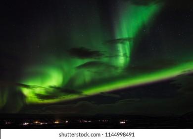 Aurora Borealis. Iceland near Myvatn lake in winter. Beautiful dancing northern lights over winter mountain landscape