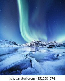 Aurora Borealis, Lofoten islands, Norway. Nothen light and reflection on the lake surface. Winter landscape at the night time. Norway travel - image