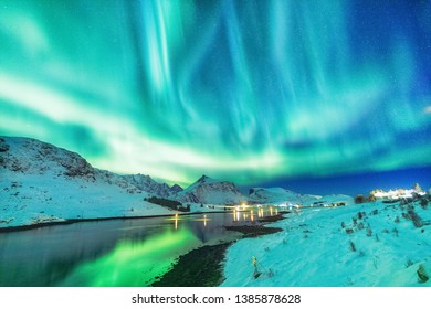 Aurora Borealis natural phenomenon on Lofoten Islands in Norway, Scandinavia, Europe. Night sky with northern lights over mountains and road reflected in fjord. Night winter landscape with aurora.