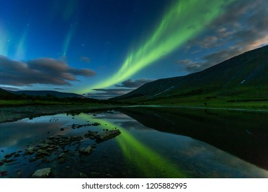 aurora borealis in the night sky cut the mountains, reflected in the water. Yamal. Russia
