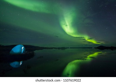 Aurora Borealis (Northern lights) above a camping tent in the Icelandic wilderness near lake