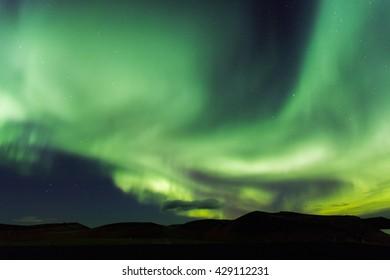 Aurora borealis. Northern lights in Iceland Myvatn. Stars in night sky illuminated by northern lights
