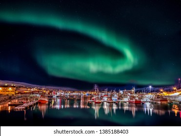Aurora Borealis (Northern Lights) over the harbour at Batsfjord, Finmark, arctic circle, Norway, with colourful illuminated boats, and reflections in still water.