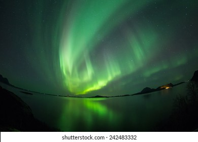 Aurora Borealis (Northern lights) Over coastal sea with reflection and fish-eye lens