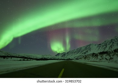 Aurora Borealis Northern Lights over empty road and snow capped mountains