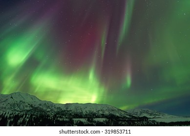 Aurora Borealis Northern Lights over snow capped mountains