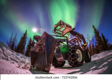 Aurora borealis northern lights over the snow remuval tracktor