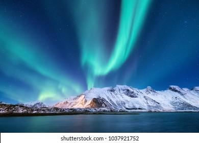 オーロラ・ボレアリスはノルウェーのロフォテン諸島にいる。山の上の緑の北の光。夜空と極光。オーロラと水面に映る夜の冬の風景。ナチュラルバック