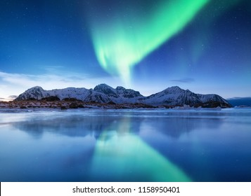 Aurora borealis on the Lofoten islands, Norway. Green northern lights. Night sky with polar lights. Night winter landscape with aurora and reflection on the ice surface.