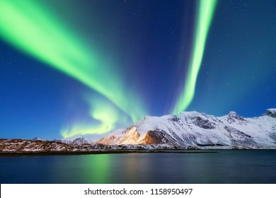 Aurora borealis on the Lofoten islands, Norway. Green northern lights above mountains. Night sky with polar lights. Night winter landscape with aurora and reflection on the water surface.