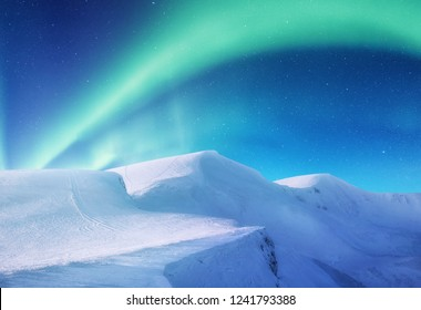 Aurora borealis on the Lofoten islands, Norway. Green northern lights above mountains. Night sky with polar lights. Night winter landscape with aurora. Natural background in the Norway