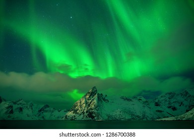 Aurora Borealis on the Lofoten Islands, Norway. Green northern lights above mountains. Night sky with polar sky above arctic circle. Winter landscape with aurora reflection on the water surface.