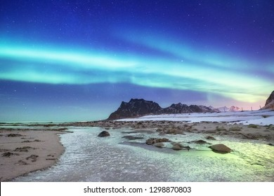 Aurora borealis on the Lofoten islands, Norway. Night sky with polar lights. Night winter landscape with aurora and reflection on the water surface. Norway-image