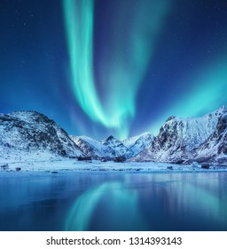 Aurora borealis on the Lofoten islands, Norway. Green northern lights above mountains. Night sky with polar lights. Night winter landscape with aurora and reflection on the water surface. Norway-image