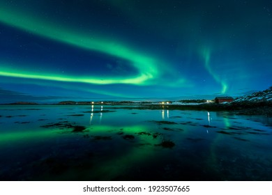 Aurora Borealis on the night sky above the sea. Winter night in Norway. Pure Northern nature.