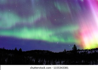 Aurora Borealis and Orion constellation over northern Taiga in Finnish Lapland.