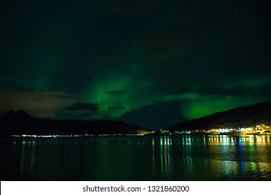 Aurora Borealis over Fjord Gratangen at Årstein in early winter on cloudy day, Nothern lights
