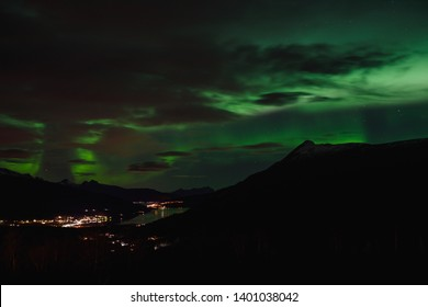 Aurora Borealis over Fjord Gratangen in early winter on cloudy day, Nothern lights