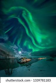 Aurora borealis over little island Sandvikholmen with footbridge near Hamn, Senja, Norway