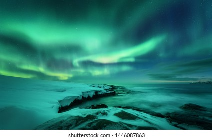Aurora borealis over ocean. Northern lights in Teriberka, Russia. Starry sky with polar lights and clouds. Night winter landscape with aurora, sea with stones in blurred water, snowy mountains. Travel