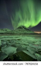 The aurora borealis over Skoddebergvatnet lake in northern Norway in winter.