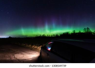 Aurora borealis (polar lights) and reflection on the car