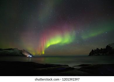 Aurora borealis (Polar lights). View to Steinfjord on Senja island (Oksan on Background) - Lofoten islands, Norway