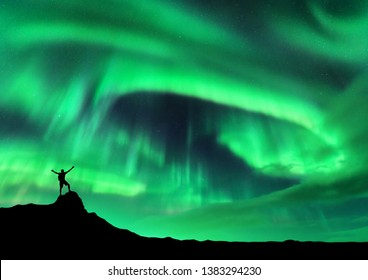 Aurora borealis and silhouette of a man with raised up arms on the mountain peak. Lofoten islands, Norway. Aurora and happy man. Sky with stars and polar lights. Night landscape with aurora and people
