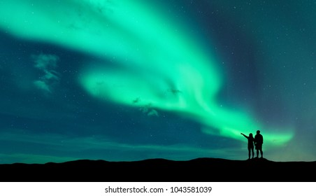 Aurora borealis and silhouette of standing man and woman who pointing finger on northern lights. Lofoten islands,Norway. Aurora. Sky with stars and polar lights. Night landscape with aurora and couple