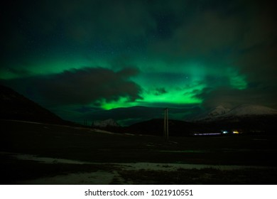 Aurora borealis, stars and clouds , with mountains, and a power line in the foreground