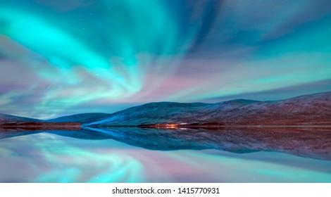 Aurora Borealis in Tromso, Norway in front of the Norwegian fjord - Winter season.