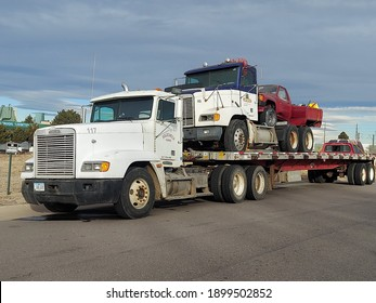 AURORA, COLORADO - JANUARY 21, 2021: A heavy truck with Iowa license plate carries two smaller vehicles on its flatbed trailer
